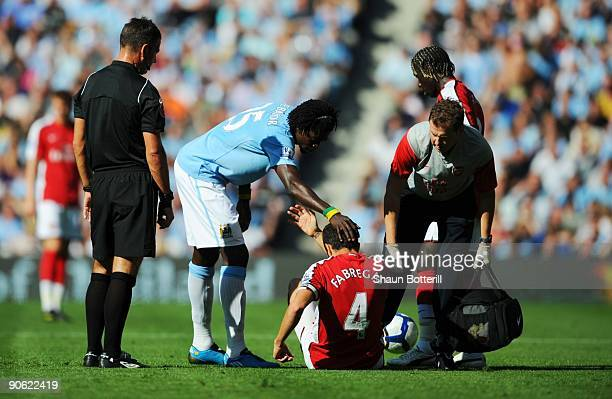 Francesc Fabregas of Arsenal is helped to his feet by Emmanuel Adebayor of Manchester City after being fouled during the Barclays Premier League...