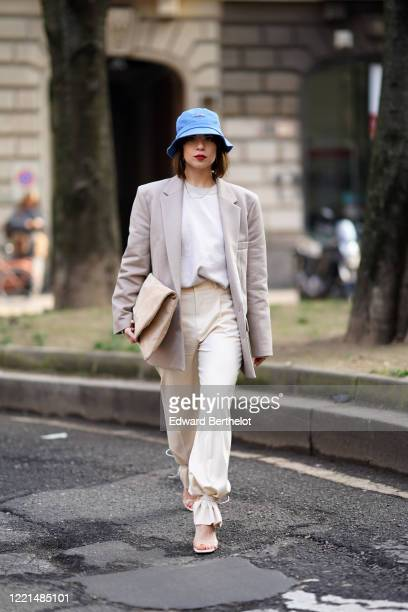 Francesca Cina wears a blue bob hat, a gray oversized blazer jacket, a white t-shirt, white pants, a bag, shoes, outside Calcaterra, during Milan...