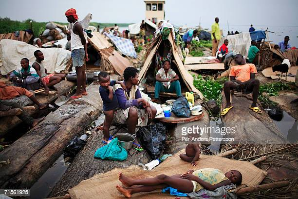 Francesca Mboyo prepares to cook for her six children while traveling on a boat made of big trees on the Congo River on June 30 2006 outside Mbandaka...