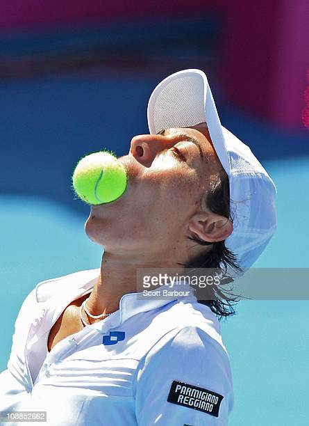 Francesca Schiavone of Italy bites a tennis ball after putting it in her mouth during her match against Samantha Stosur of Australia during day two...