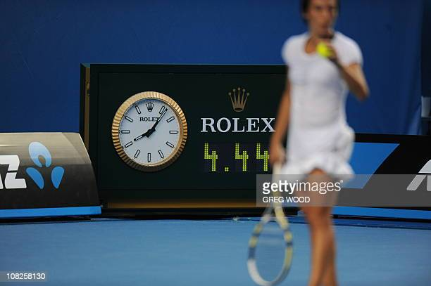 Francesca Schiavone of Italy prepares to serve for match point against Svetlanda Kuznetsova of Russia in front of the clock showing the match...
