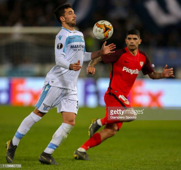 Francesco Acerbi of SS Lazio controls the ball in front of Ever banega of Sevilla during the UEFA Europa League Round of 32 First Leg match between...