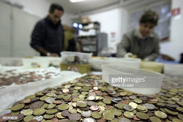 Francesco an AIDS patient and a Caritas employee process coins from the Trevi Fountains November 28 2005 in Rome Italy Tourists from all over the...