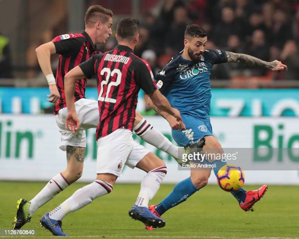 Francesco Caputo of Empoli FC is challenged by Andrea Conti of AC Milan during the Serie A match between AC Milan and Empoli at Stadio Giuseppe...