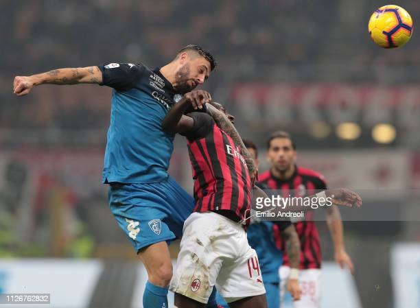 Francesco Caputo of Empoli FC jumps for the ball against Tiemoue Bakayoko of AC Milan during the Serie A match between AC Milan and Empoli at Stadio...