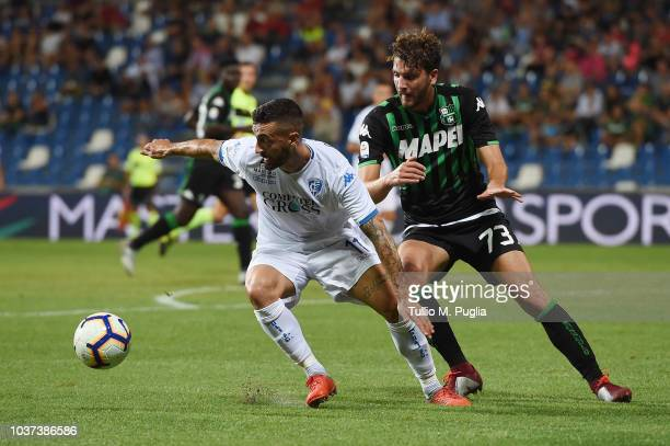 Francesco Caputo of Empoli is challenged by Manuel Locatelli of Sassuolo during the serie A match between US Sassuolo and Empoli at Mapei Stadium...