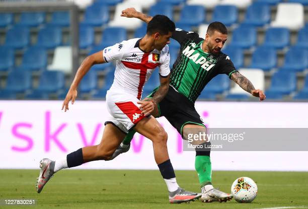 Francesco Caputo of US Sassuolo competes for the ball with Cristian Romero of Genoa CFC during the Serie A match between US Sassuolo and Genoa CFC at...