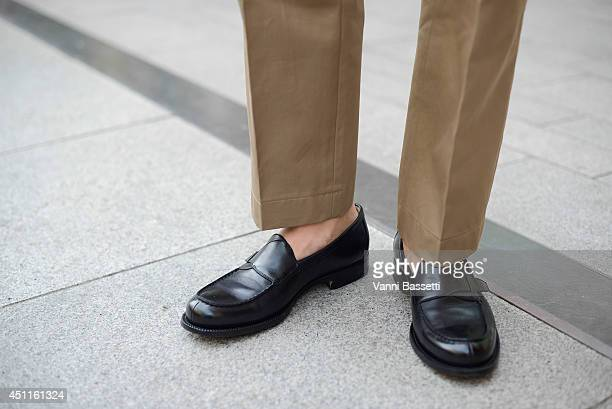 Francesco Casarotto poses in YSL pants and Ermenegildo Zegna shoes after Girgio Armani show on June 24 2014 in Milan Italy