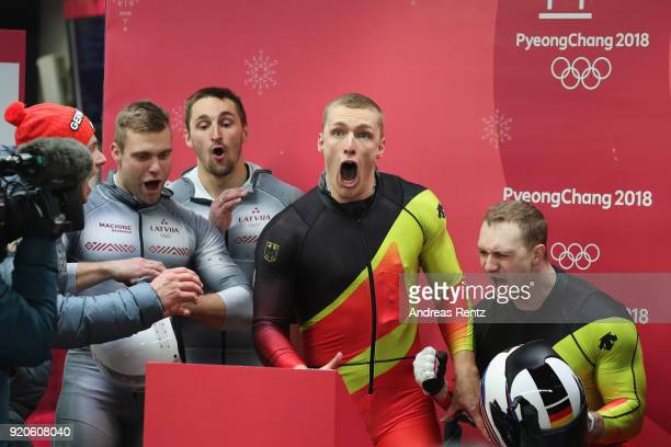 Francesco Friedrich and Thorsten Margis of Germany react as they watch the final run by Justin Kripps and Alexander Kopacz of Canada during the Men's...