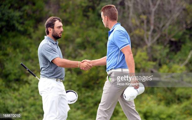Francesco Molinar of Italy shakes hands with Henrik Stenson of Sweden after winning 21 on day one of the Volvo World Match Play Championship at...