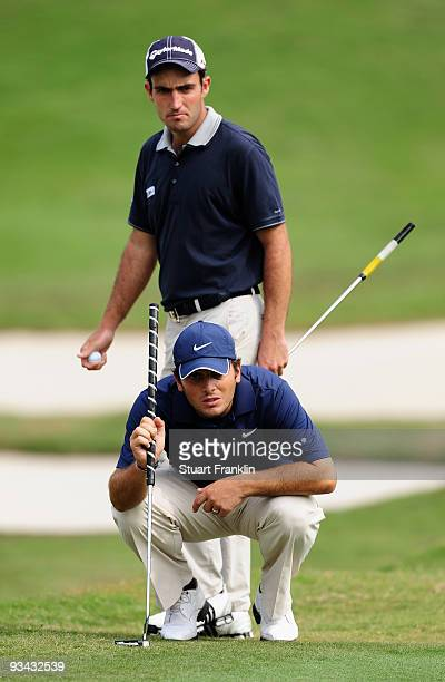 Francesco Molinari and Edoardo Molinari of Italy line up a putt on the 14th hole during Fourball on the first day of the Omega Mission Hills World...