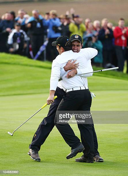 Francesco Molinari of Europe celebrates holing a putt to halve their match on the 18th green with Edoardo Molinari during the Fourball Foursome...