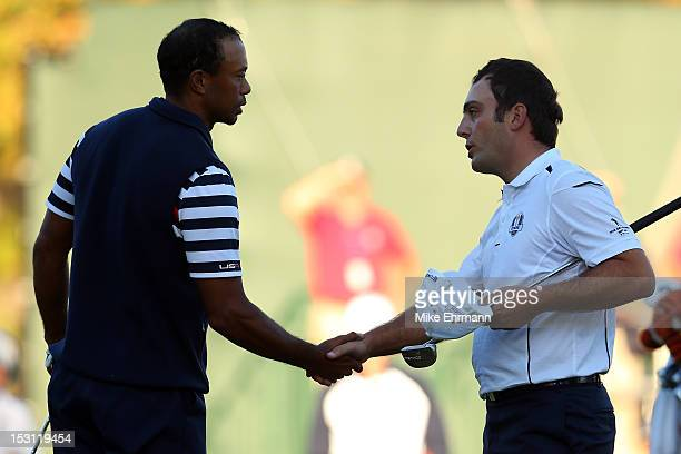 Francesco Molinari of Europe shakes hands with Tiger Woods of the USA on the 18th green after halving his match with Woods during the Singles Matches...