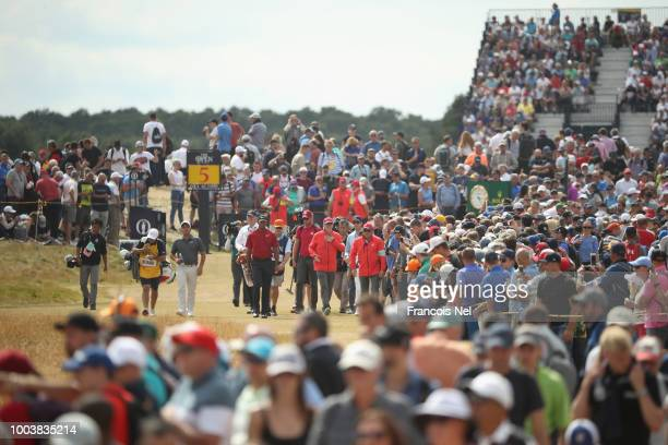 Francesco Molinari of Italy and Tiger Woods of the United States walk down the fifth fairway during the final round of the 147th Open Championship at...