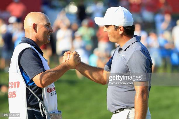 Francesco Molinari of Italy celebrates with his caddie after winning the Quicken Loans National during the final round at TPC Potomac on July 1, 2018...