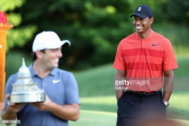 Francesco Molinari of Italy celebrates with the trophy after winning the Quicken Loans National as Tiger Woods looks on during the final round at TPC...