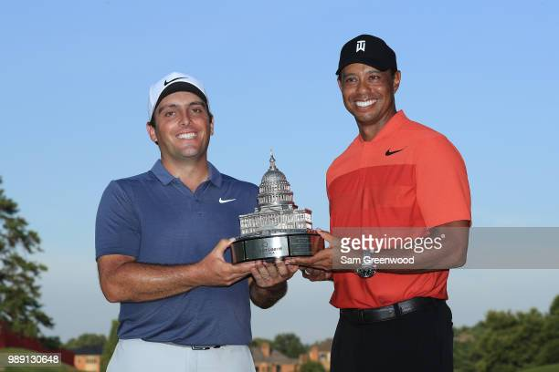 Francesco Molinari of Italy celebrates with the trophy and Tiger Woods after winning the Quicken Loans National during the final round at TPC Potomac...