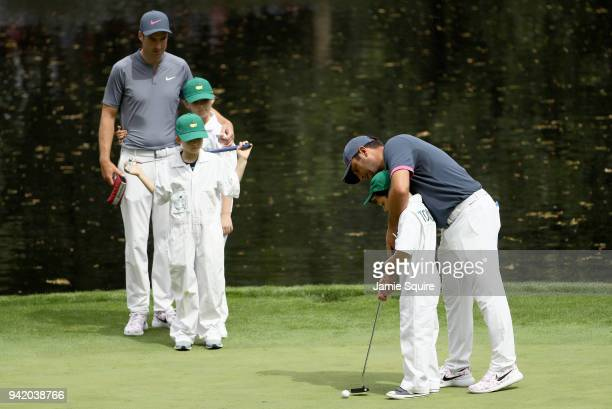 Francesco Molinari of Italy helps son Tommaso Molinari putt as Ross Fisher of England looks on during the Par 3 Contest prior to the start of the...