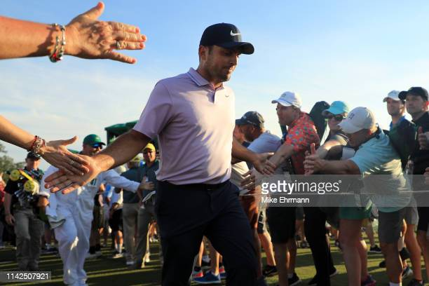 Francesco Molinari of Italy high fives patrons as he walks off the 18th green during the third round of the Masters at Augusta National Golf Club on...