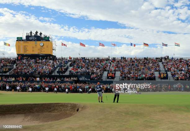 Francesco Molinari of Italy holes the winning putt on the 18th green watched by his playing partner Tiger Woods of the United States during the final...