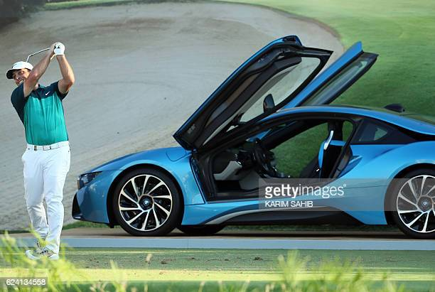 Francesco Molinari of Italy plays a shot near a BMW i8 hybrid sports car during day two of the DP World Tour Championship at Jumeirah Golf Estates on...