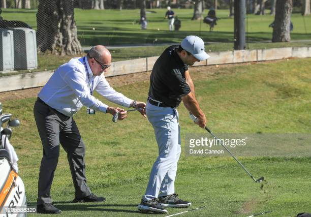 Francesco Molinari of Italy works with his coach Dennis Pugh during practice for the Genesis Invitational at The Riviera Country Club on February 11...