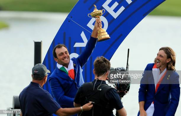 Francesco Molinari of Itlay and the European Team raises the Ryder Cup watched by Tommy Fleetwood after their 17.5-10.5 win over the United States...