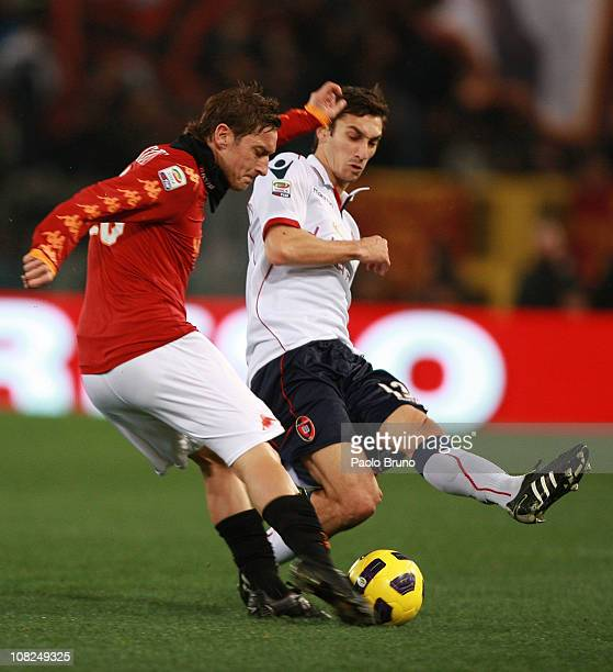 Francesco Totti of AS Roma competes for the ball with Davide Astori of Cagliari Calcio during the Serie A match between AS Roma and Cagliari Calcio...