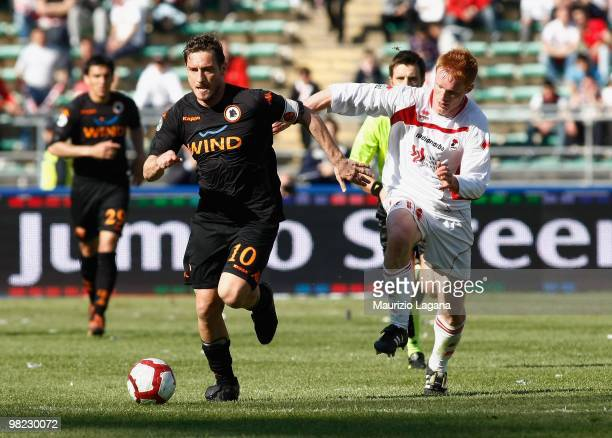 Francesco Totti of AS Roma is challenged by Alessandro Gazzi of AS Bari during the Serie A match between AS Bari and AS Roma at Stadio San Nicola on...