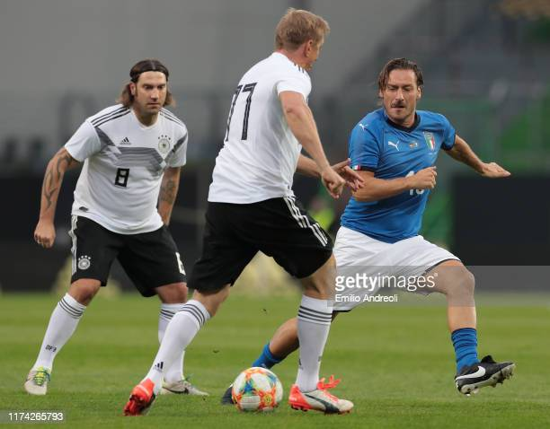 Francesco Totti of Azzurri Legends competes for the ball with Marko Rehmer of DFB-All-Stars during the friendly match between DFB-All-Stars and...