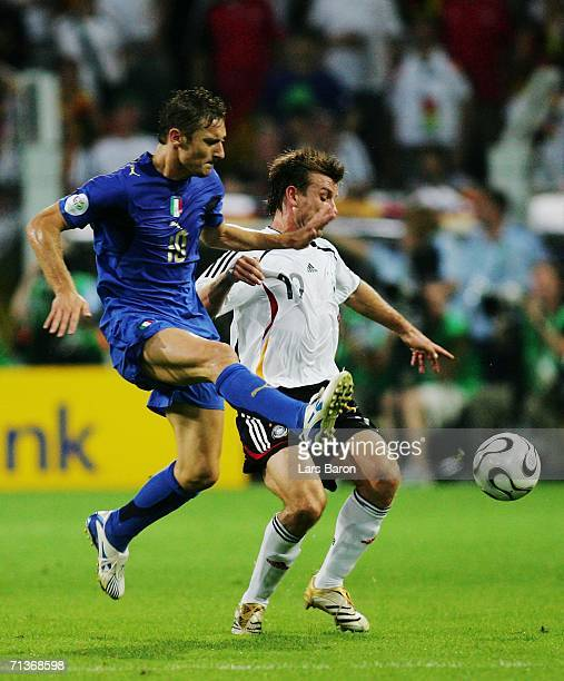 Francesco Totti of Italy fights for the ball with Bernd Schneider of Germany during the FIFA World Cup Germany 2006 Semifinal match between Germany...
