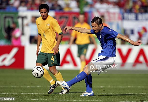 Francesco Totti of Italy shoots on goal as Tim Cahill of Australia looks on during the FIFA World Cup Germany 2006 Round of 16 match between Italy...