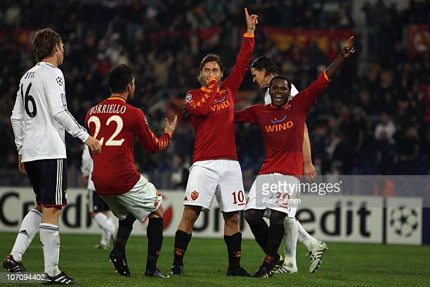 Francesco Totti of Roma celebrates his team's third goal with team mates Marco Borriello and Fabio Simplicio as Martin Demichelis of Muenchen reacts...