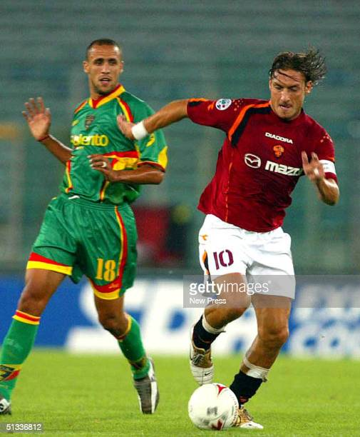 Francesco Totti of Roma moves the ball past Guillermo Giacomazzi of Lecca during the Italian Serie A match between Lecce v Roma September 22 2004 at...