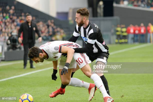Francesco Zampano of Udinese competes with Hakan Calhanoglu of AC Milan during the serie A match between Udinese Calcio and AC Milan at Stadio Friuli...