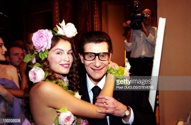 Franch model Laetitia Casta with flowers in her hair hugs French fashion designer Yves Saint Laurent at Yves Saint Laurent Fashion Show 2000 on...