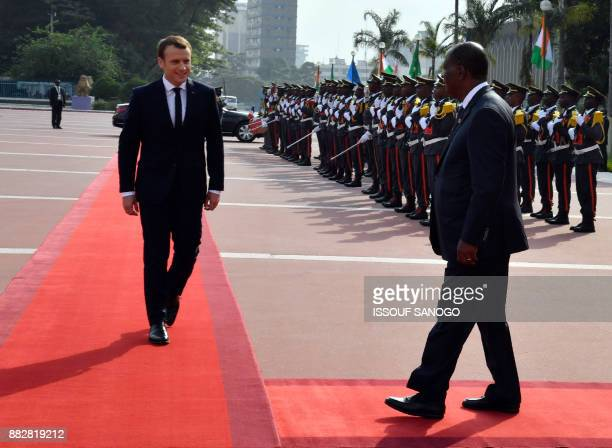 Franch president Emmanuel Macron is welcomed by Ivorian president Alassane Ouattara upon his arrival at the presidential palace in Abidjan on...