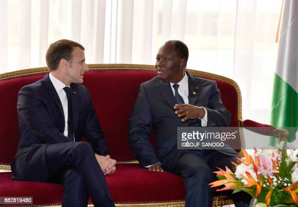 Franch president Emmanuel Macron speaks with Ivorian president Alassane Ouattara upon his arrival at the presidential palace in Abidjan on November...