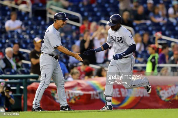 Franchy Cordero of the San Diego Padres celebrates with third base coach Glenn Hoffman after hitting a solo home run during a game against the...