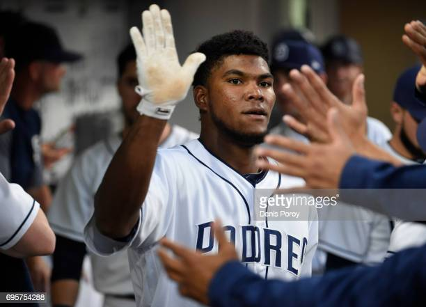 Franchy Cordero of the San Diego Padres is congratulated after hitting a solo home during the third inning of a baseball game against the Cincinnati...