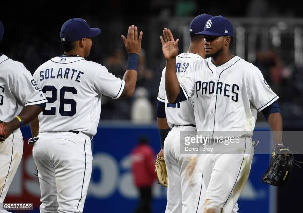 Franchy Cordero of the San Diego Padres right and Yangervis Solarte high five after beating the Cincinnati Reds 93 in a baseball game at PETCO Park...