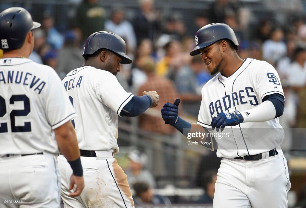 Franchy Cordero #33 of the San Diego Padres, right, is congratulated by Jose Pirela #2 as Christian Villanueva #22 looks on after Cordero hit a three-run home run during the fourth inning of a baseball game against the New York Mets at PETCO Park on April 28, 2018 in San Diego, California.