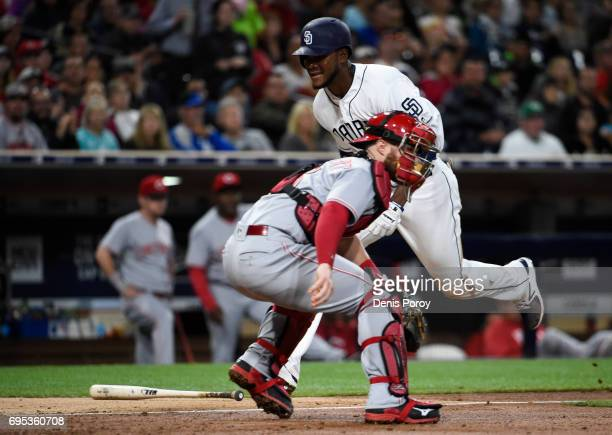 Franchy Cordero of the San Diego Padres scores ahead of the throw to Tucker Barnhart of the Cincinnati Reds during the fourth inning of a baseball...