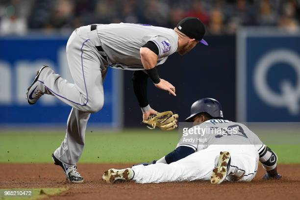 Franchy Cordero of the San Diego Padres steals second base as Trevor Story of the Colorado Rockies attempts a tag at second base during the game at...