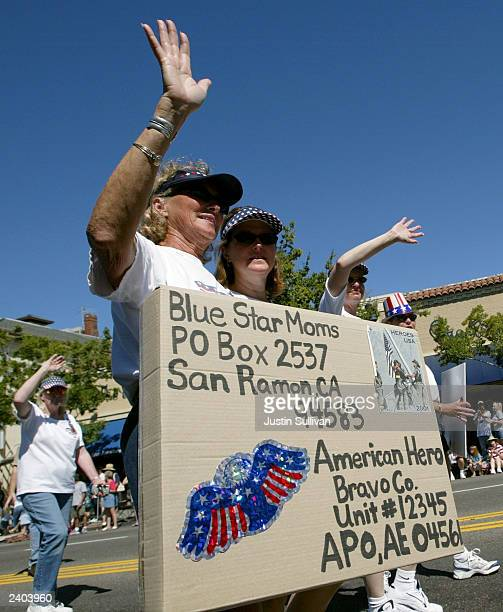 Francie Roberts of the group Blue Star Moms waves as she holds a large care package to troops during a parade honoring troops August 16 2003 in...