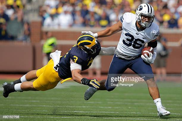 Francis Bernard of the Brigham Young Cougars carries the ball as Desmond Morgan of the Michigan Wolverines dives for a tackle to drive him out of...