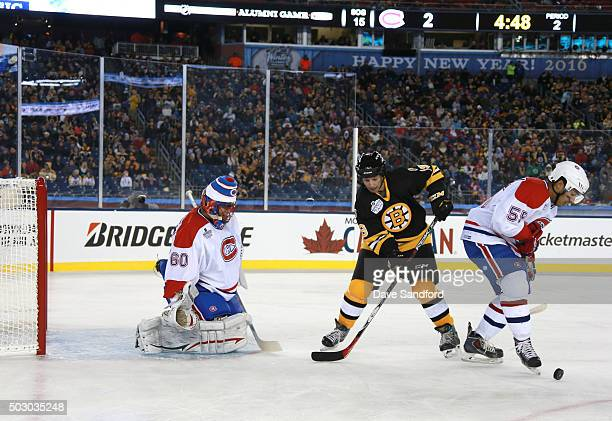 Francis Bouillon of the Montreal Canadiens Alumni Team plays the puck as Rob DiMaio of the Boston Bruins Alumni Team looks for the loose puck in...