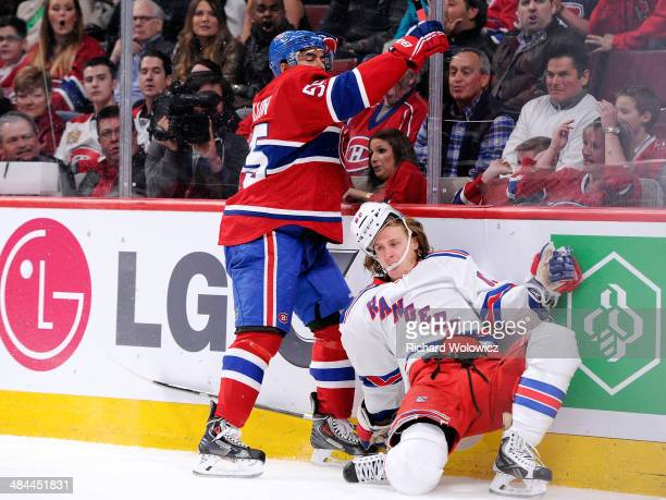 Francis Bouillon of the Montreal Canadiens body checks Carl Hagelin of the New York Rangers during the NHL game at the Bell Centre on April 12 2014...