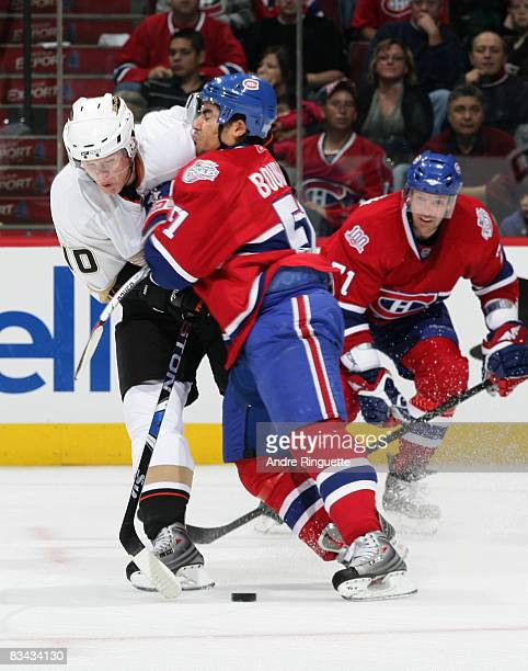 Francis Bouillon of the Montreal Canadiens bodychecks Corey Perry of the Anaheim Ducks off the puck at the Bell Centre on October 25 2008 in Montreal...