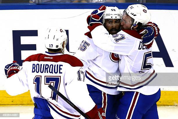 Francis Bouillon of the Montreal Canadiens celebrates with his teammates Rene Bourque and David Desharnais after scoring a goal in the second period...